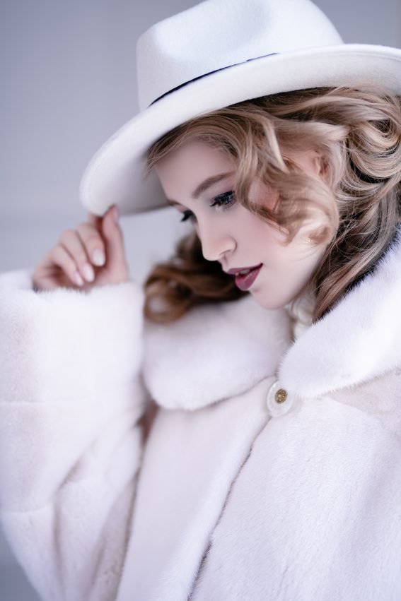 Beautiful Woman in White Fur Coat and a Hat
